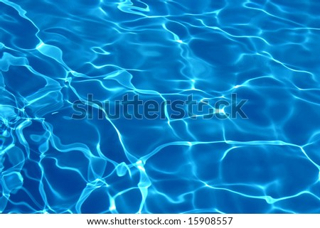 Wavy blue pool water reflecting the sky - stock photo