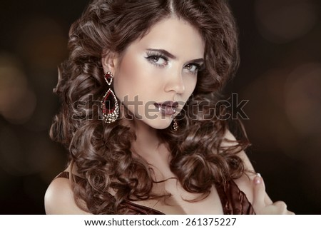 Wavy hair. Attractive girl with makeup. Jewels. Earring. Expressive eyes stare. Elegant lady over studio dark background. Luxury style. - stock photo