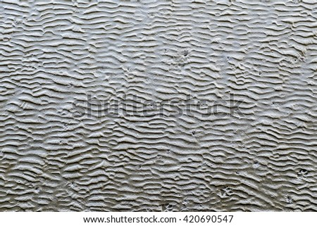 Wavy Pattern of the sandy ocean floor at low tide with striking  - stock photo