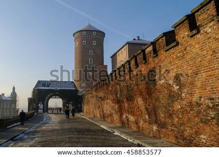 Wawel royal castle in winter morning. Main gate,Sandomierska Tower, entrance to the castle, Krakow, Poland - stock photo