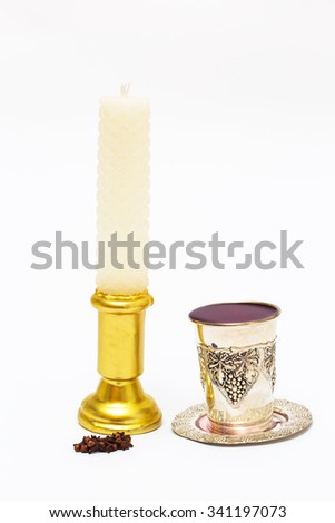 Wax candle with a glass of wine and fragrant cloves. Havdalah. - stock photo