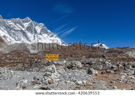 Way to Island Peak sign installed on a rocky trail with Lhotse mountain on the background. Trail leading to the Island Peak base camp. Blue sky and Lhotse mountain scenery on the way to Island Peak. - stock photo