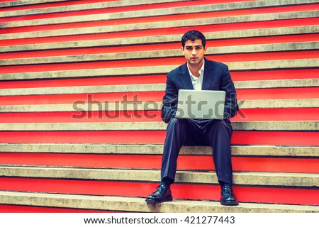 Way to Success. East Indian American College Student studying in New York, wearing black suit, white shirt, leather shoes, sitting on stairs, working on laptop computer. Instagram filtered effect. - stock photo
