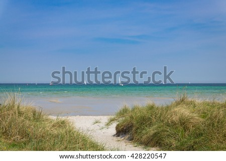 Way to the beach of the Baltic Sea with sail ships in the background, Germany - stock photo