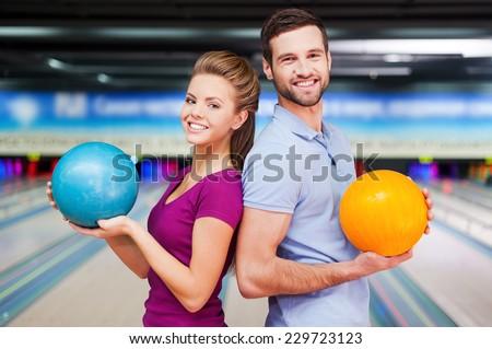 We are a team. Cheerful young man and women looking over shoulders and holding bowling balls while standing against bowling alleys  - stock photo