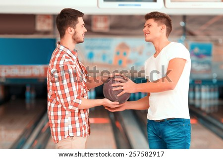 We are a team. Two friends looking at each other and holding a bowling ball while standing against bowling alleys  - stock photo
