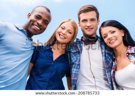 We are all good friends. Low angle view of four happy young people bonding and looking at camera with smile with blue sky in the background - stock photo