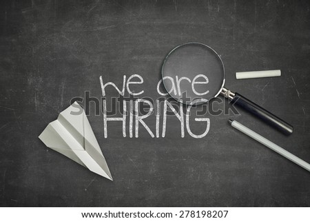 We are hiring concept on black full frame blackboard with magnifying glass - stock photo