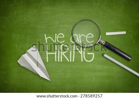 We are hiring concept on green full frame blackboard with magnifying glass - stock photo