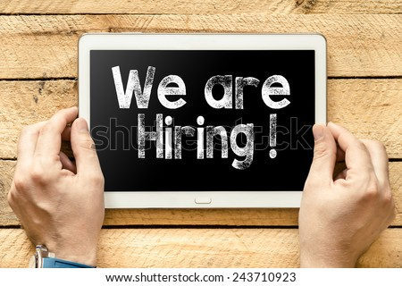We are hiring On PC. Hands with Tablet PC with we are hiring text on wooden background - stock photo