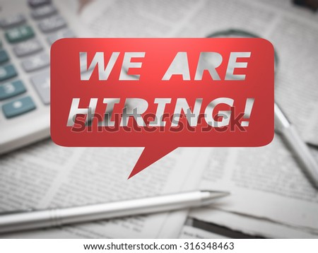 we are hiring with speech bubble on office desk background - stock photo