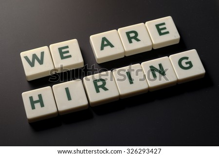 We are hiring word tiles on chalkboard, business conceptual - stock photo