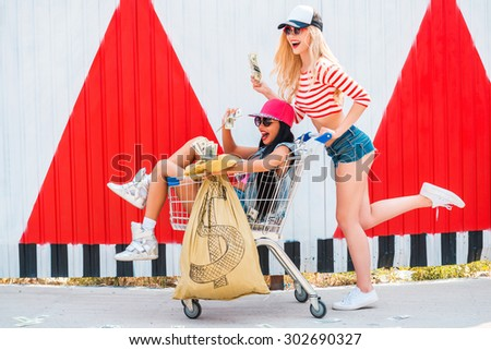 We are rich! Excited young women holding money bag and sitting in the shopping cart while her female friend pushing it and running - stock photo
