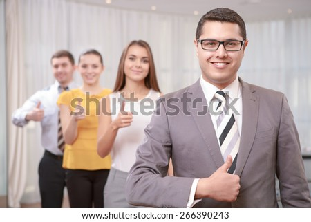 We are the best. Confident young businessman shows sign thumb up as well as his colleagues standing behind on background - stock photo