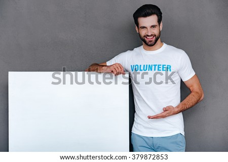 We can help to community! Confident young man in volunteer t-shirt pointing on white boardand looking at camera with smile while standing against grey background - stock photo