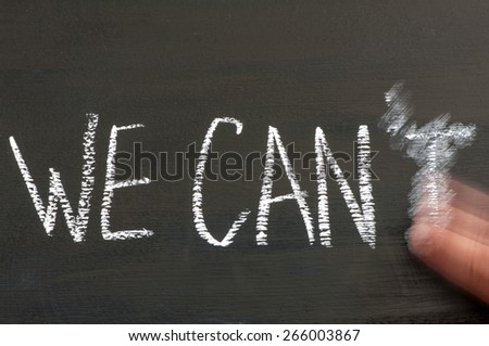 We Can't replaced by We Can message isolated on black background, letter T erased by a moving hand. Chalk drawing on blackboard. Business Concept image. - stock photo