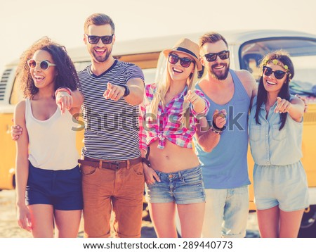 We choose you! Group of joyful young people pointing you and smiling while standing on the beach with retro minivan in the background  - stock photo