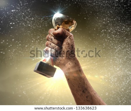 We did it! Hand tighten the cup winner against lightning dark sky. - stock photo