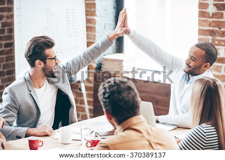 We did it! Two young men doing high-five while their coworkers sitting at the office table - stock photo