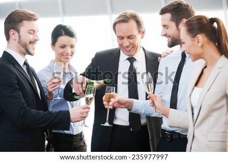 We got a contract! Group of happy business people holding flutes with champagne and smiling while standing close to each other indoors - stock photo