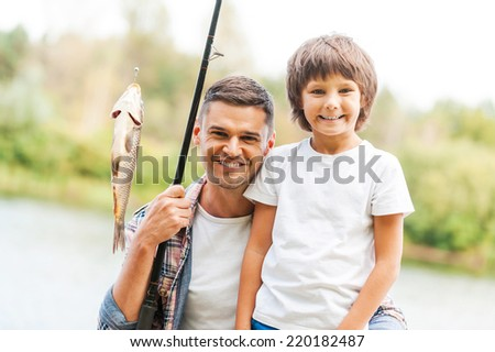 We have caught it together! Father and son looking at camera and smiling while man holding fishing rod with big fish on the hook  - stock photo