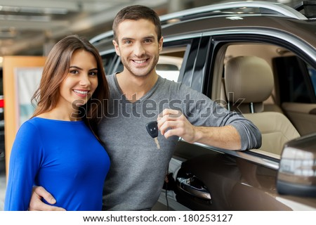 We have made the right choice. Handsome young men standing near the car at the dealership hugging his girlfriend and holding a key - stock photo