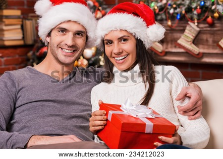 We love Christmas! Beautiful young loving couple bonding to each other and smiling while woman holding gift box with Christmas Tree in the background  - stock photo