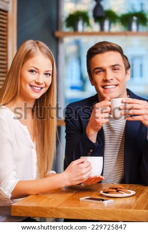 We love spending time together. Beautiful young couple looking at camera and smiling while enjoying coffee in cafe together  - stock photo