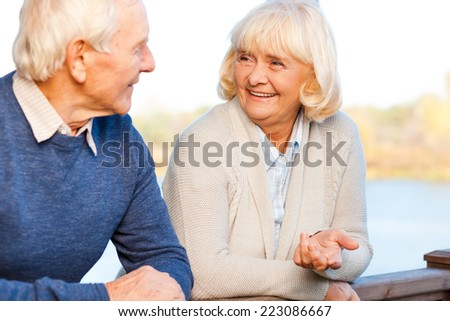 We love spending time together. Happy senior couple talking to each other and smiling while standing outdoors - stock photo