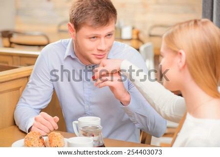 We love spending time together. Young handsome man kissing his mates hand while enjoying coffee in cafe together  - stock photo