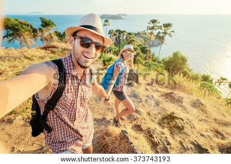 We love traveling and trekking! Adventure Selfie. Caucasian young loving couple taking selfie while they walking on mountains near the sea. - stock photo