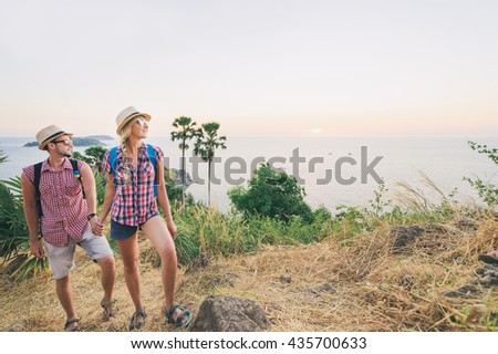 We love travelling and trekking! Caucasian young loving couple walking on mountains near the sea. - stock photo