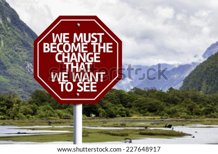 We Must Become The Change That We Want to See written on red road sign with landscape background - stock photo