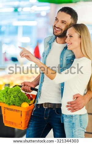 We should buy this! Cheerful young couple smiling and pointing away while standing in a food store - stock photo