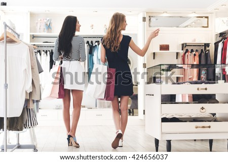 We should look at new dresses! Rear view of two beautiful women with shopping bags looking away with smile while walking at the clothing store - stock photo