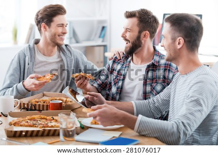 We work hard but have fun doing it! Three happy young men eating pizza together while sitting in the office  - stock photo