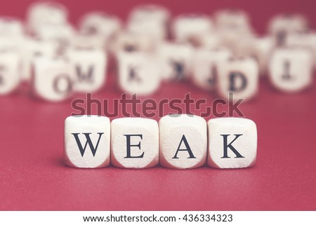 Weak word written on wood cube with red background - stock photo