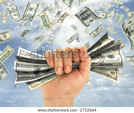 Wealth idea in a metaphor of rain of dollars. The hand holds some dollars. - stock photo