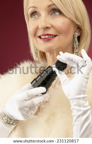Wealthy Mature Woman Putting on Perfume - stock photo