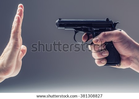 Weapon  gun. Men's hand holding a gun. The second hand is defending. - stock photo