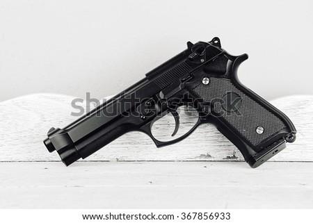 Weapon series. Modern U.S. Army handgun close-up on vintage wooden table background. pistols (Black & White) - stock photo