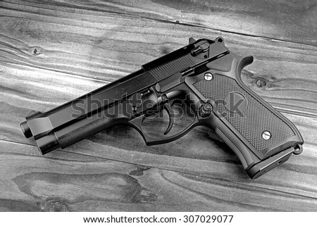 Weapon series. Modern U.S. Army handgun M9 close-up on grey wooden background. (Black & White) - stock photo