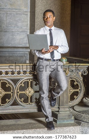 Wearing a white shirt, a black tie, gray pants, a young handsome black college student is standing by a railing in a hallway on a campus, working on a laptop computer. / Working Outside - stock photo