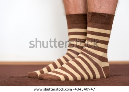 Wearing comfortable striped socks at home. - stock photo