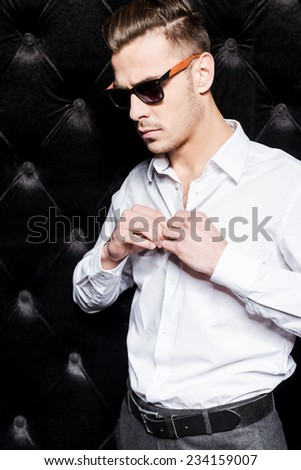 Wearing his favorite shirt. Handsome young man in sunglasses buttoning his white shirt while standing against black background  - stock photo