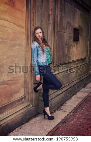 Wearing patterned underwear, Denim jacket, legging pants, hight heels, bending a leg, a teenage girl is leaning against an old fashion style wall, looking at you. Instagram Sutro effect.  - stock photo