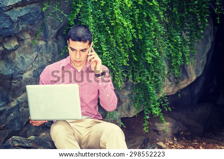 Wearing red, white patterned shirt, a young college student sitting against rocks with green leaves on campus, reading, working on laptop computer, calling on cell phone in same time. Instagram effect - stock photo