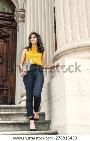 Wearing sleeveless orange shirt, striped pants, high heels, carrying laptop computer, a young East Indian American college student walking down stairs outside office building on campus, looking up. - stock photo