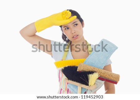 Weary woman holding brushes and mops and wiping her brow - stock photo