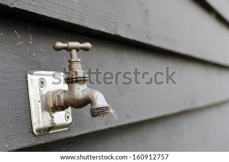 Weather beaten outdoor tap against a black wooden wall - stock photo
